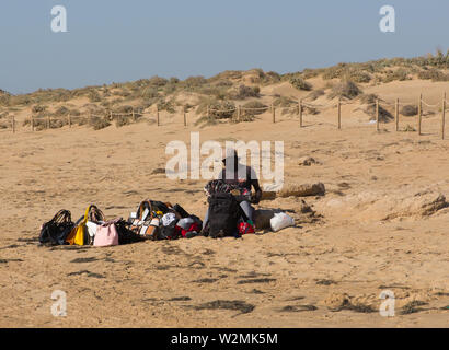 Black beach salesman preparing his goods ready for a day of selling at Guardamar del Segura, Costa Blanca, Spain - Stock Image