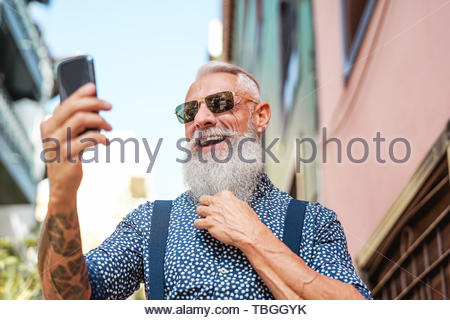Bearded senior using mobile phone outdoor - Hipster mature man having fun with new trends smartphone apps - Stock Image