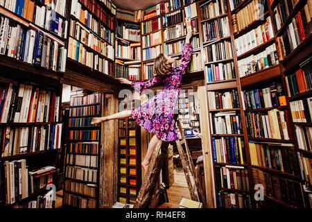Carefree woman on ladder reaching for book in library - Stock Image
