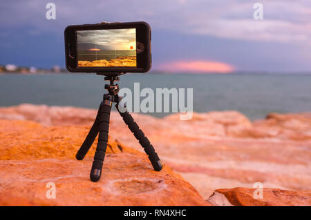 Mobile phone on a mini tripod recording a time lapse at East Point in Darwin, Northern Territory, Australia. - Stock Image