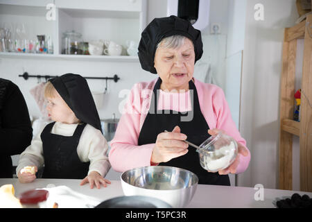 Family making pancakes. An old woman putting the dough on the pan - Stock Image