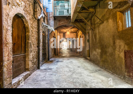 Old houses along narrow cobblestone street in medieval town Villefranche-sur-Mer on French Riviera, France - Stock Image
