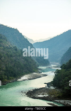 Stunning view of some green mountain peaks with the Sacred Ganges River flowing between them in Rishikesh, India. - Stock Image