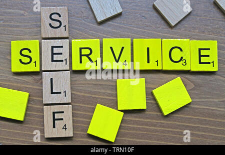 Self-Service spelt out in yellow and wooden Scrabble letters - Stock Image