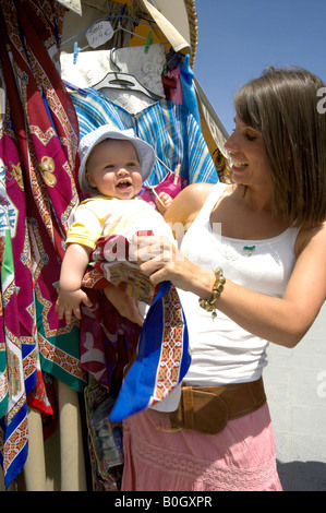 Mother and toddler shopping for colourful fabrics and shawls, Mijas Pueblo, Costa del Sol, Andalucia, Spain - Stock Image