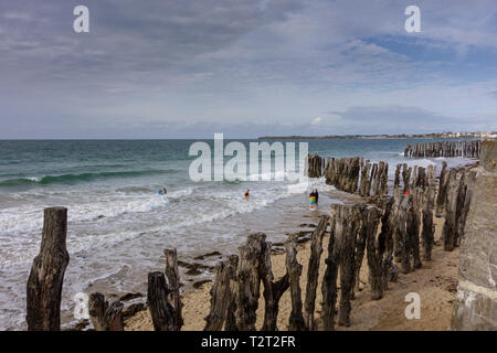 View of sea and groynes along promenade at seafront, Saint Malo, Brittany, France - Stock Image
