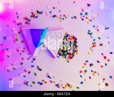 Christmas decoration triangle git boxes with colorful candies spread as confetti under purple party lights for celebration - Stock Image