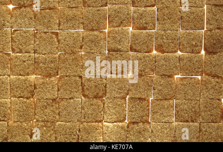 Background image of brown sugar cubes underlit to show gaps in the sugar - Stock Image