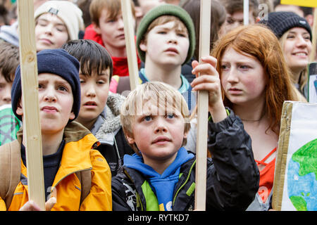 Bristol, UK. 15th Mar, 2019. Bristol college students and school children carrying climate change placards and signs are pictured as they protest outside Bristol City Hall. The pupils who also went on strike last month walked out of school again today as part of a countrywide coordinated strike action to force action on climate change policy. Credit: lynchpics/Alamy Live News - Stock Image