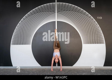 woman doing a handstand practicing yoga outside in front of a geometric symmetrical pattern on a wall. - Stock Image
