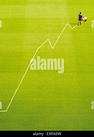 A groundsman painting a profit graph on a pitch - Stock Image