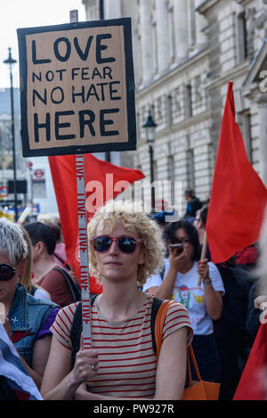 London, UK. 13th October 2018.   A woman holds a placard 'LOVE NOT FEAR NO HATE HERE' at the rally in London to oppose racism  and fascism close to where the racist, Islamophobic DFLA were ending their march on Whitehall bringing together various groups to stand in solidarity with the communities the DFLA attacks. The event was organised by Stand Up To Racism and Unite Against Fascism. Peter Marshall/Alamy Live News - Stock Image