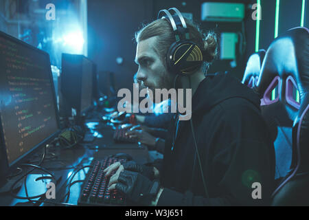 Concentrated bearded guy in wired headset sitting at table and examining script on computer monitor - Stock Image