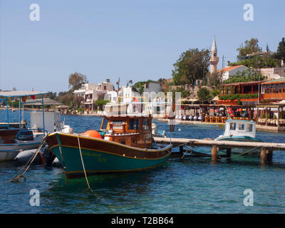 Turkey, Bodrum peninsula, Mugle province - the harbour of Gumusluk with boat, restaurant on the beach, mosque in the background - Stock Image