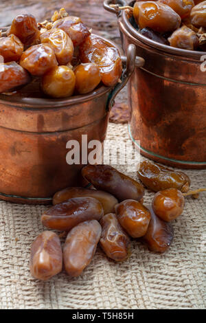 Authentic Tunisian Deglet Nour dried dates with soft honey-like taste in copper buckets - Stock Image