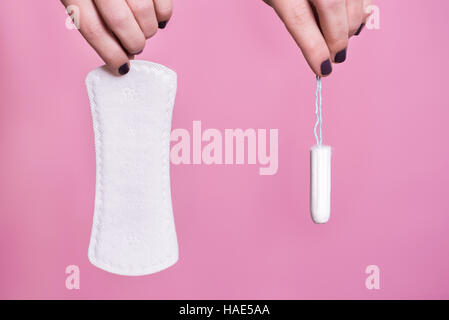 Women holding a sanitary napkin and tampon - Stock Image