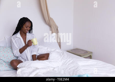 Beautiful African woman with long braids relaxing on her bed in the morning - Stock Image