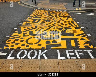 LOOK LEFT! Helpful advice to pedestrians who need to cross a busy road in the Barbican area of London, England. Photo © COLIN HOSKINS. - Stock Image