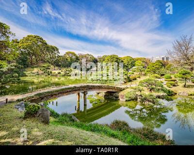 5 April 2019: Tokyo, Japan - Pond and bridge in Kiyosumi Garden, a traditional style landscape garden in Tokyo. - Stock Image