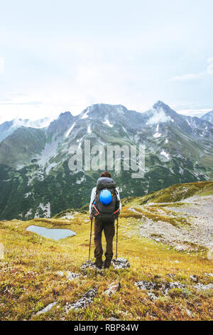 Adventurer hiking in mountains solo traveling adventure lifestyle summer vacations activity outdoor backpack gear - Stock Image
