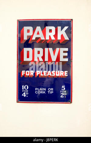 Old metal advert for PARK DRIVE cigarettes adorning a heriatage steam railway in UK showing rust marks and blemishes - Stock Image