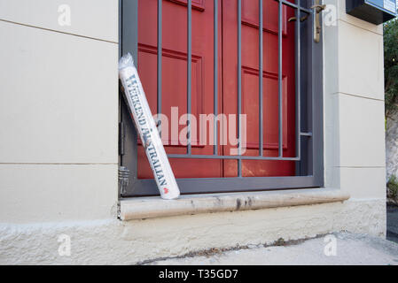 A rolled up Australian Newspaper sits on a doorstep of a home in the Sydney suburb of Surry Hills in New South Wales, Australia - Stock Image
