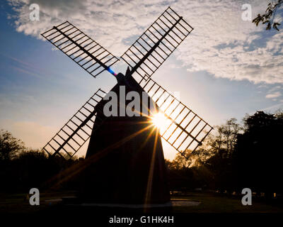 Eastham Windmill, Eastham, Cape Cod, Massachusetts in silhouette with sun flare behind it. - Stock Image
