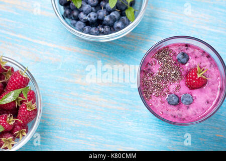 smoothie with blueberries and raspberries, chia seeds  in a glass, fresh blueberries and raspberries on old wooden background. view from above - Stock Image