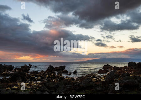 Looking west towards the island of La Gomera from a pebble beach in Playa San Juan at dawn on a cloudy day,  Tenerife, Canary Islands, Spain - Stock Image