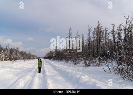 A man and a woman birding on a snow covered road in a cold winter day. Duluth, Minnesota, USA. - Stock Image