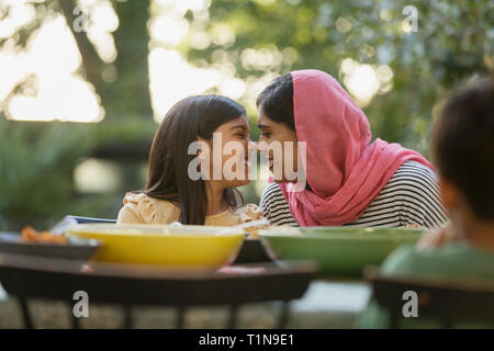 Affectionate mother in hijab rubbing noses at dinner table - Stock Image