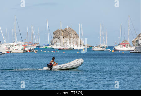 tan woman operating a inflatable tender in St Barts - Stock Image