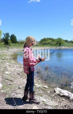 Blond girl fishing at the edge of a water hole - Stock Image