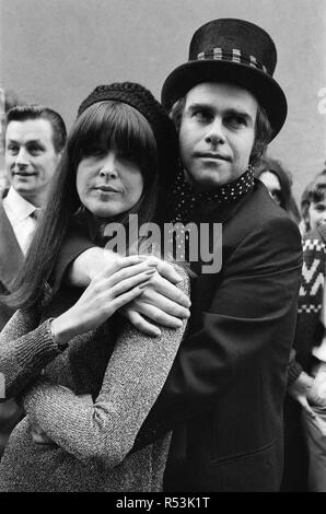 Wearing a top hat, Elton John, at a small studio in Ladbroke Grove to make a promotional film for his new single. Giving the film the feeling of the 1960's in the style of 'Ready Steady Go', Elton invited Cathy McGowan to take part. 5th October 1978. - Stock Image