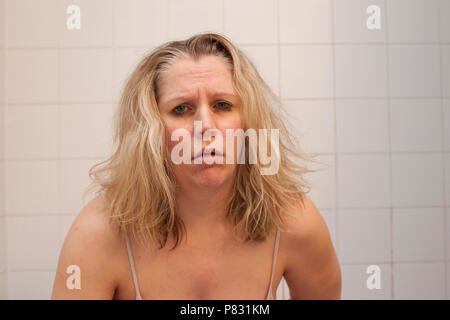 Woman with black bruised eyes and messy hair looks like she is ready to be sick or throw up - Stock Image