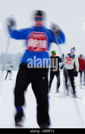 Camera motion blur of cross country skiers. - Stock Image