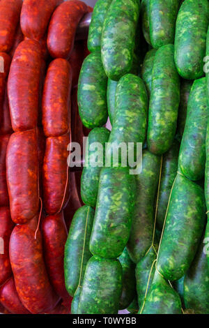 Red and green chorizo for sale at Mercado el Tepe, a huge urban market in Santiago de Queretaro, Mexico - Stock Image