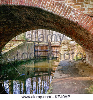 Derelict lock on the Basingstoke Canal,  seen from under an accomodation bridge (or occupation bridge}; Deepcut - Stock Image