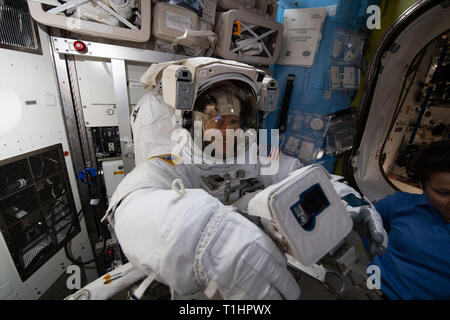 NASA astronaut Christina Koch is fitted in a U.S. spacesuit and checks out a spacewalk camera less than two weeks before beginning her first spacewalk in the Quest Airlock  March 18, 2019 in Earth Orbit. - Stock Image
