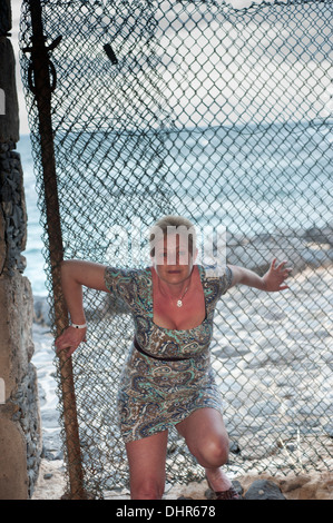 female posing in mesh fence with sea as backdrop - Stock Image