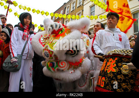 London, UK: 14 February 2010: Festival participants preapre for the dragon dance at a restaurant entrance. Chinese New Year celebration in London. Photo Credit: David Mbiyu - Stock Image