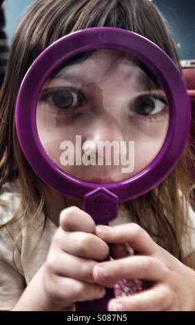 Toddler girl looking through magnifying glass - Stock Image