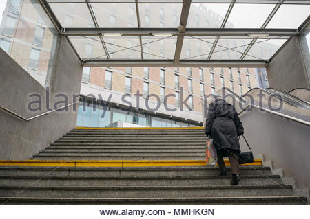 Older woman with shopping bag walking on stairs of the Kaponiera underground passage in Poznan, Poland - Stock Image