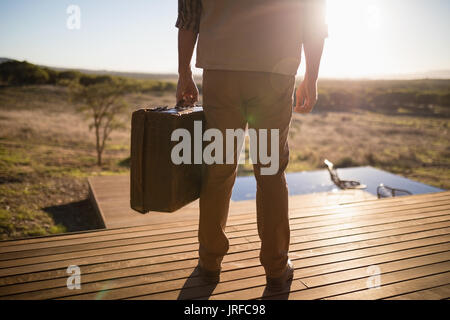 Low section of man with suitcase standing on wooden plank - Stock Image
