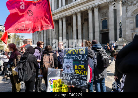 London, UK. 15th April 2019. A small group of people met in front of St Paul's Cathedral for a protest organised by the Green Anti-Capitalist Front, Earth Strike and London Students for Climate Justice. While supporting the  environmentalist actions by Extinction Rebellion they wanted to go to workplaces at the heart of the capitalist system in the City of London to make it clear that climate struggle is class struggle. Peter Marshall/Alamy Live News - Stock Image