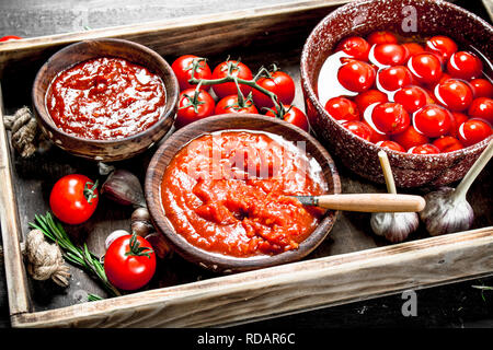 Tomato sauce with fresh and marinated tomatoes. On black background. - Stock Image