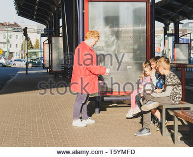 Poznan, Poland - April 18, 2019: Blond woman with red jacket standing with food close by sitting kids on a public transport stop in the Rataje bus sta - Stock Image