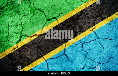 United Republic of Tanzania flag on dry earth ground texture background - Stock Image