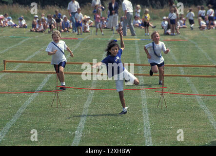 primary school children competing in hurdle race during sports day - Stock Image