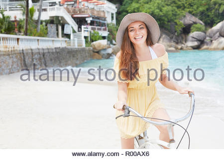 Young woman wearing yellow dress riding bicycle on beach - Stock Image